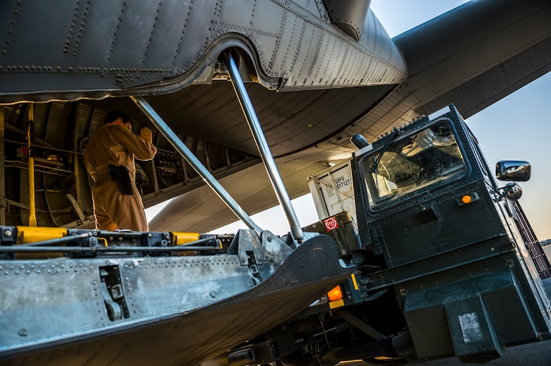 Master Sgt. Scott Francesangeli directs a K-loader to the back of a C-130H Hercules July 20, 2014, in Southwest Asia. Loadmasters ensure all cargo and personnel to be transported are placed and secured properly to ensure the plane can take off and fly safely. Francesangeli is a 737th Expeditionary Airlift Squadron C-130H loadmaster. (U.S. Air Force photo/Staff Sgt. Jeremy Bowcock)