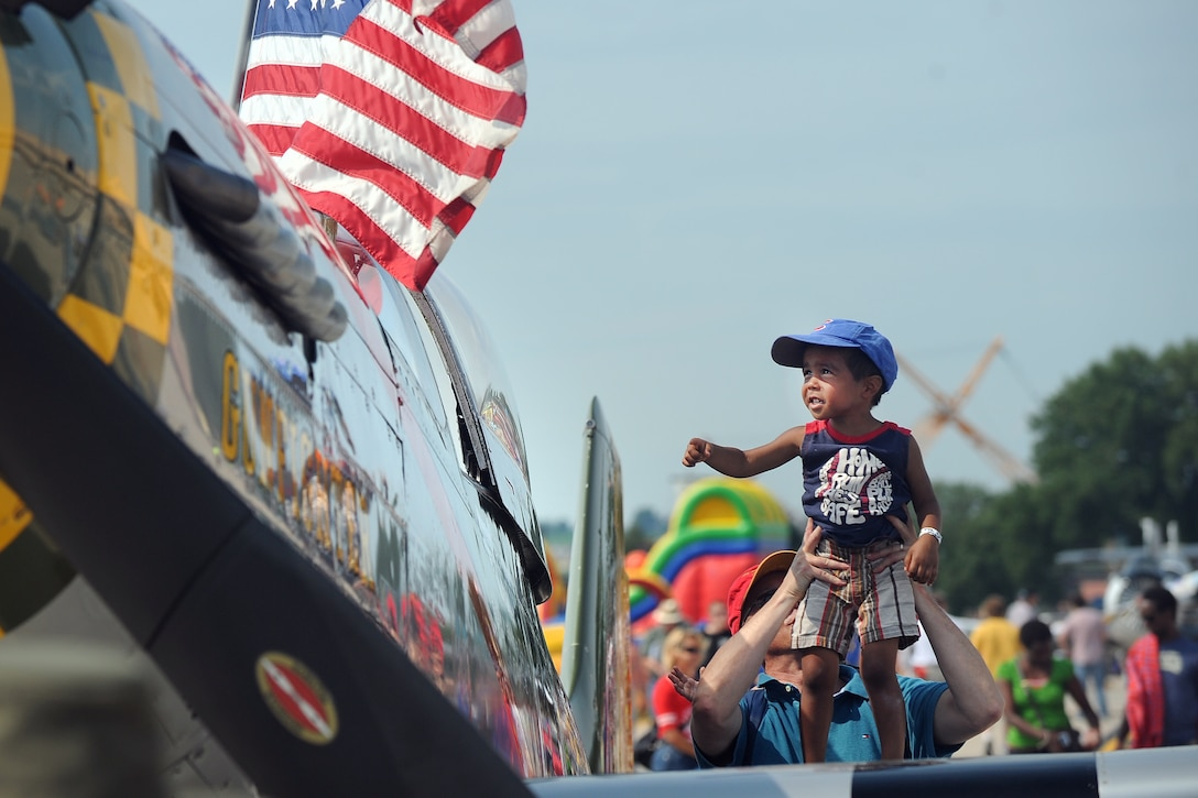 Four-year-old James Aldendifer is lifted onto the wing of the P-51 Mustang by his father Mark while attending the 2014 Defenders of Freedom Open House and Air Show July 19, 2014, on Offutt Air Force Base, Neb. Record crowds gathered at Offutt AFB to attend the event. (U.S. Air Force photo/Josh Plueger)
