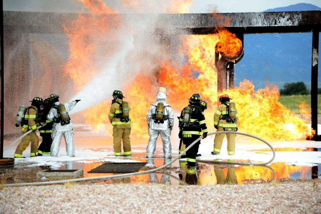 Service members with the Peterson Air Force Base Fire Department conduct live training with the Cimarron Hills Fire Department July 21, 2014, at a special training facility on Peterson AFB, Colo. All firefighters in attendance had a chance to practice specialized tactics against a real fire. The all steel training structure 'fueled' by a massive propane tank is designed to resemble a C-130 Hercules airframe and provides firefighters with a realistic scenario to train with and maintain skills. (U.S. Air Force photo/Michael Golembesky)