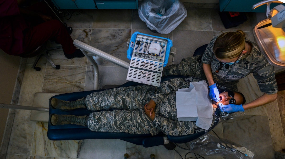 Capt. Leslie Jones, examines the teeth of Master Sgt. Francesca Seehausen July 22, 2014, at Incirlik Air Base, Turkey. The 39th Medical Group dental clinic provides care to the base populace to keep service members mission ready and deployable. Jones is a 39th MDG dentist and Seehausen is the 39th MDG dental flight chief.  (U.S. Air Force photo/Senior Airman Nicole Sikorski)