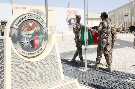 Soldiers with the Kingdom of Jordan fold their flag during a ceremony aboard Camp Leatherneck, Helmand province, Afghanistan, July 23, 2014. The ceremony marked the end of mission for the Jordanian army serving with Regional Command (Southwest).