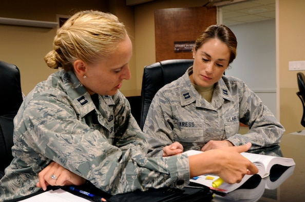 Capt. Laura Buchholtz, 30th Space Wing chief of military justice, and Capt. Sarah Kress, Area Defense Counsel, go over courtroom procedures, July 25, 2014, Vandenberg Air Force Base, Calif. With military members being held to high standards of conduct under the Uniform Code of Military Justice, the availability of fair legal representation is an Air Force priority. (U.S. Air Force photo by Senior Airman Shane Phipps/Released)