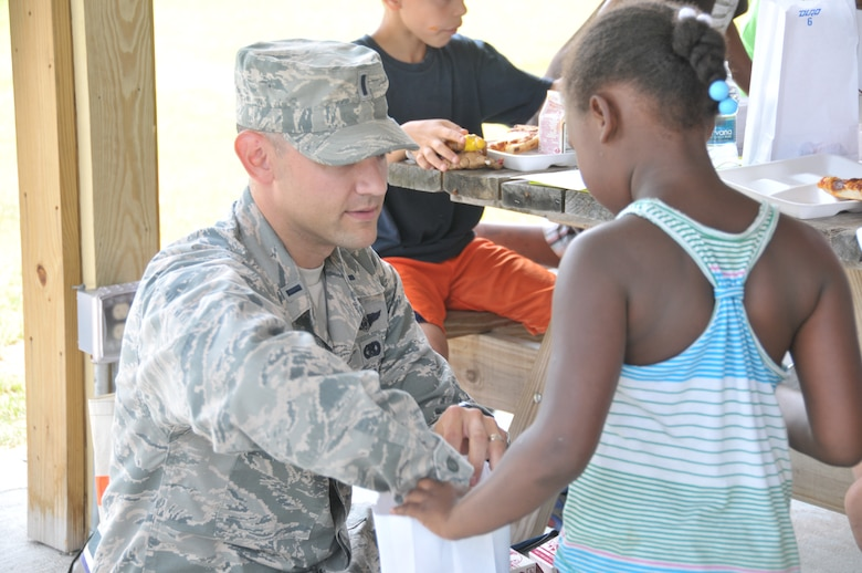 First Lt. Jared Semerad, 109th Logistics Readiness Squadron, hands out lunches to youth at Steinmetz Park in Schenectady, New York, July 25, 2014. About 30 Airmen from the 109th Airlift Wing volunteered throughout the week to help with Schenectady Inner City Ministry's Summer Lunch Program. The ministry has been providing free lunches to youth throughout Schenectady for 20 years. (U.S. Air National Guard photo by Tech. Sgt. Catharine Schmidt/Released)