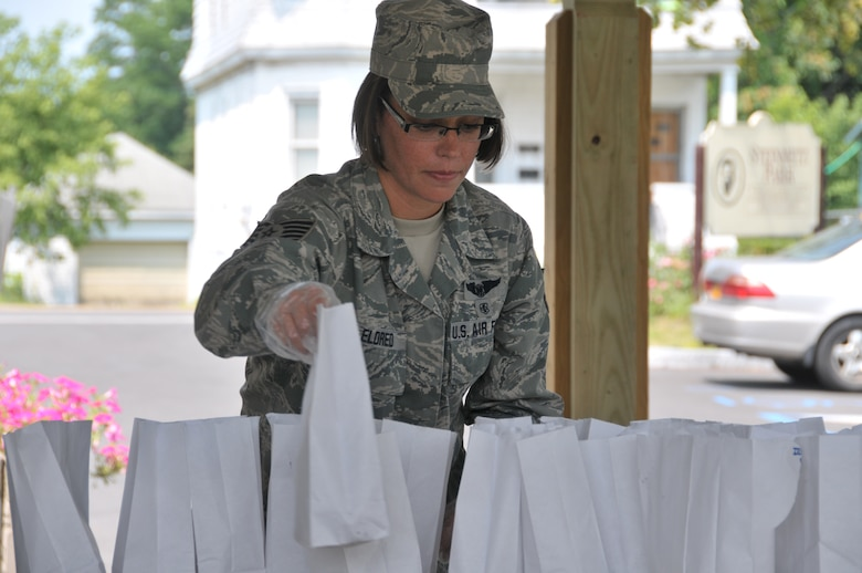 Tech. Sgt. Sara Eldred, 139th Aeromedical Evacuation Squadron, hands out lunches to youth at Steinmetz Park in Schenectady, New York, July 25, 2014. About 30 Airmen from the 109th Airlift Wing volunteered throughout the week to help with Schenectady Inner City Ministry's Summer Lunch Program. The ministry has been providing free lunches to youth throughout Schenectady for 20 years. (U.S. Air National Guard photo by Tech. Sgt. Catharine Schmidt/Released)