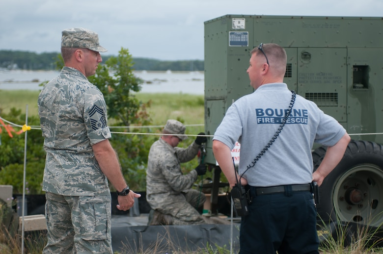 Chief Master Sgt. Jason Mello, of the 267th Combat Communications Squadron, and Lt. Greg Edgcomb, of the Bourne Fire Department oversee the assembly of a emergency medical station on July 24, 2014 on Mashnee Rd. in Bourne, Mass. The station is supplied by the 102nd Intelligence Wing, but will be manned by Bourne Fire Department members during the Pan-Mass Challenge, an annual bike-a-thon that supports the Dana-Farber Cancer Institute.(National Guard photo by Master Sgt. Aaron Smith/Released)