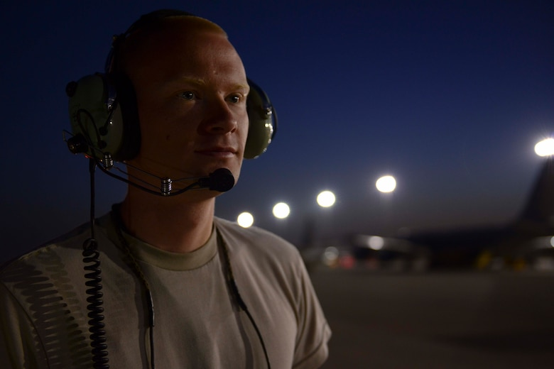 U.S. Air Force Airman 1st Class Olin Enzor, 763rd Aircraft Maintenance Unit electronics and environmental specialist, looks out at early morning maintenance operations at Al Udeid Air Base, Qatar, July 11, 2014. Enzor is deployed from Offut Air Force Base, Nebraska and hails from Macon, Georgia. (U.S. Air Force photo by Staff Sgt. Ciara Wymbs)