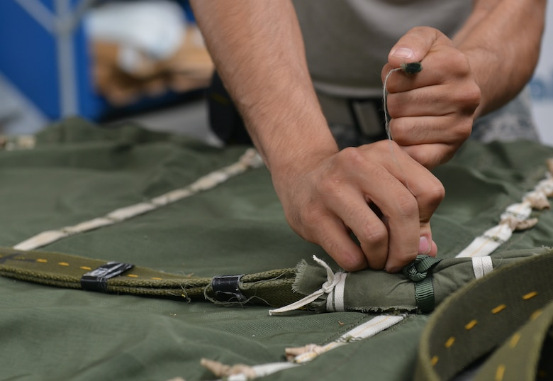 Senior Airman Brian Rodriguez, 86th Logistics Readiness Squadron aerial delivery specialist, prepares half bags July 23, 2014, Ramstein Air Base, Germany. Airmen of the aerial delivery department prepare different types of cargo parachutes and goods for air drops support missions around the world. (U.S. Air Force photo/Senior Airman Holly Mansfield)