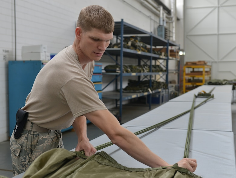 Airman 1st Class Kyle Taylor, 86th Logistics Readiness Squadron aerial delivery specialist, folds a cargo parachute July 23, 2014, Ramstein Air Base, Germany. Airmen of the aerial delivery department prepare different types of cargo parachutes and goods for air drops support missions around the world. (U.S. Air Force photo/Senior Airman Holly Mansfield)