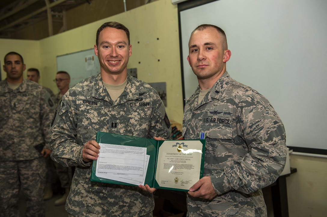 U.S. Air Force 1st Lt. Steven Butcher, 386th Expeditionary Communications Squadron operations officer, receives the Army Achievement Medal July 23, 2014 at an undisclosed location in Southwest Asia. Butcher earned the award for his outstanding support to the Delta 1-44 Air Defense Artillery Battalion, providing joint service support in the area of responsibility. He is deployed from the 21st Communications Squadron, Peterson Air Force Base, Colorado in support of Operation Enduring Freedom. (U.S. Air Force photo by Staff Sgt. Jeremy Bowcock)