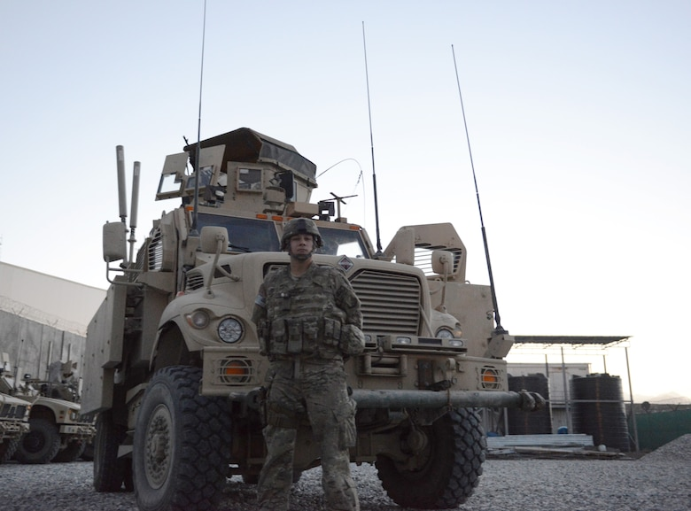 Senior Airman Julian Rangel stands by one of the mine-resistant ambush-protected vehicles that two Air Force quick reaction forces used while defending a forward operating base from a Taliban attack July 17 near Kabul Airport and Afghan air force base, Afghanistan. Rangel, who was asleep at the time the attack began, responded to the fight in shorts, t-shirt and tennis shoes under his body armor. He served as a gunner on the vehicle and laid down about 400 rounds of suppressive fire with an M240B medium machine gun during the more than four-hour firefight.  (U.S. Air Force photo/Senior Master Sgt. Mike Hammond)