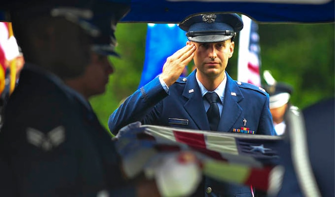 Chaplain (Capt.) Matthew Dussia salutes the remains of Capt. Robert Turnbull Sr., July 19, 2014 at Barnetts Creek Baptist Church Cemetery, Ga. Thomas County, Ga. Trunbull was one of 52 service members lost during a C-124 Globemaster crash in Alaska in 1952. Dussia is  a chaplain with the 325th Fighter Wing. (U.S. Air Force photo/Airman 1st Class Dustin Mullen)