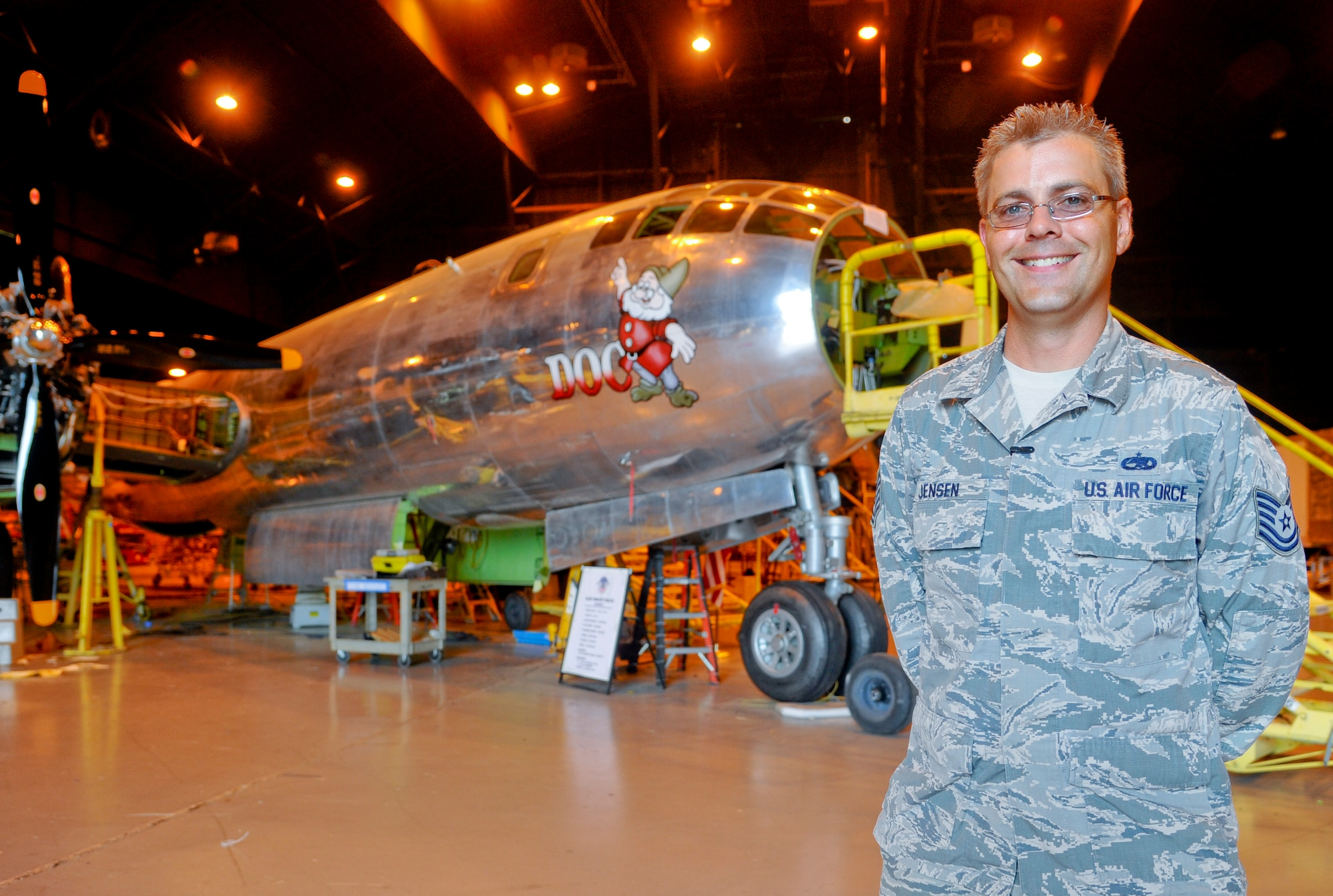 Tech. Sgt. Geoffrey Jensen stands in front of 'Doc,' a Boeing B-29 Superfortress, July 22, 2014, in Wichita, Kansas. Jensen joined a volunteer group, Doc's Friends, which is restoring the aircraft to flying condition. Jensen is the 22nd Maintenance Group logistic resource management program NCO in charge. (U.S. Air Force photo/Airman 1st Class John Linzmeier)