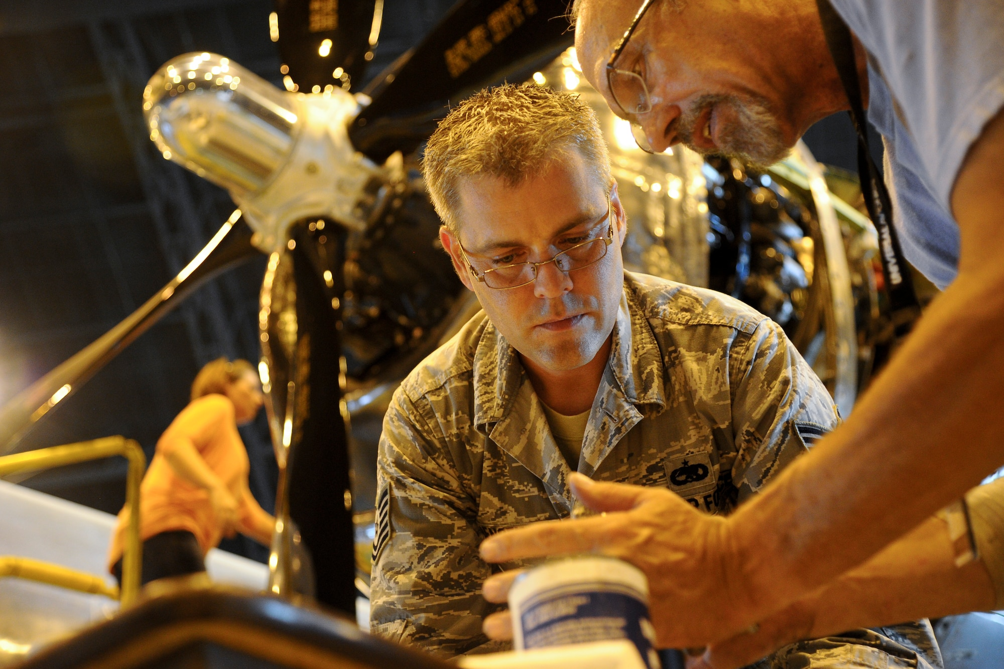 Tech. Sgt. Geoffrey Jensen places a cap on a fuel booster pump of a Boeing B-29 Superfortress, July 22, 2014, in Wichita, Kansas. Jensen along with many other volunteers are restoring the B-29 to flying condition. Jensen is the 22nd Maintenance Group logistic resource management program NCO in charge. (U.S. Air Force photo/Airman 1st Class John Linzmeier)