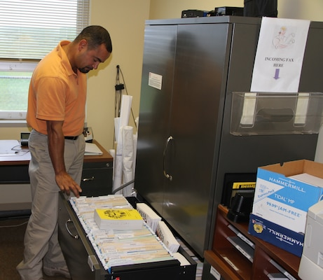 Carlos Quinones, Craney Island acting chief, points to the site's contrasting safety and health management files before and after they earned their VPP Star status.