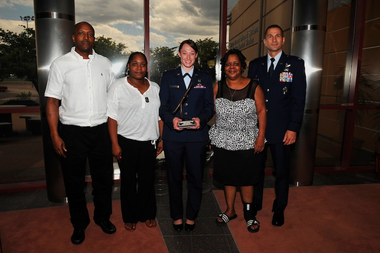 1st Lt. Laura Henderson, 2nd Space Warning Squadron Delta Crew commander, center, received the A1C Shaquille Hargrove Crew of the Year award from Hargrove's parents, left, and grandmother, second from right, July 25, 2014, at the 460th Operations Group Mission Control Station on Buckley Air Force Base, Colo. This award was created to honor Hargrove, who was killed in an incident July 2013 in downtown Denver. The award is presented to the crew that demonstrates the highest level of excellence within the squadron. (U.S. Air Force photo by Senior Airman Phillip Houk/Released)