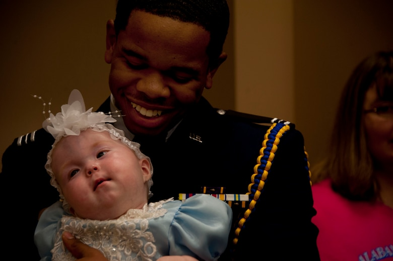 U.S. Air Force ROTC cadet Damarius Pettway, military volunteer, holds a pageant participant in his arms at the Alabama Angels Pageant July 26, 2014. The pageant recognizes specials needs participants of all ages and gender. Pettway volunteered for the event along with approximately two dozen members from Maxwell Air Force Base. (U.S. Air Force photo by Staff Sgt. Natasha Stannard)