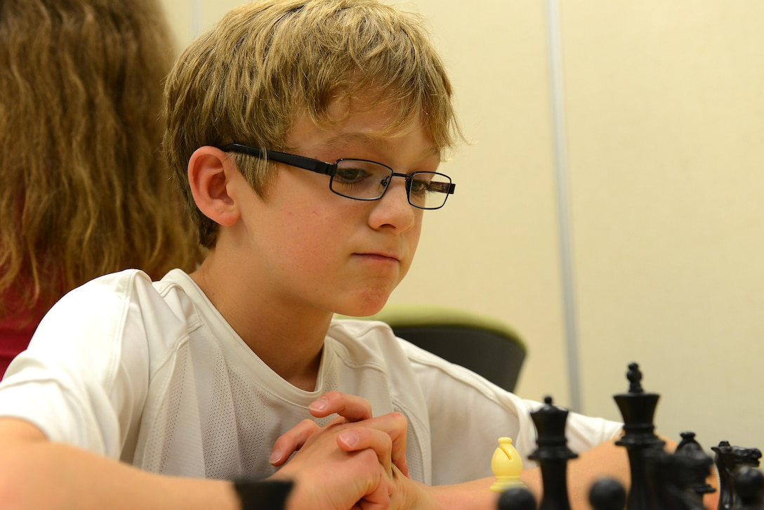 Caleb Hammon, 11-year-old son of U.S Air Force Lt. Col. Troy Hammon, U.S. Air Forces Central chief of contract and fiscal law, contemplates his next move during a chess match at the chess club at Shaw Air Force Base, S.C., July 22, 2014. Caleb started playing chess in 2007, and is furthering his knowledge and skills through the club. (U.S. Air Force photo by Airman 1st Class Diana M. Cossaboom/Released)