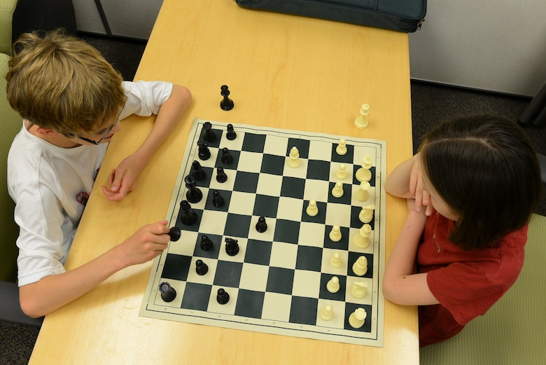 Caleb Hammon, 11-year-old son of U.S Air Force Lt. Col. Troy Hammon, U.S. Air Forces Central chief of contract and fiscal law, and Victoria Hobbs, 9-year-old daughter of Staff Sgt. Sharla Hobbs, 31st Intelligence Squadron, Detachment 1, senior tactics analyst, play chess at Shaw Air Force Base, S.C., July 22, 2014. The chess club has a total of 18 participants who take turns using the chess boards to hone their chess skills. (U.S. Air Force photo by Airman 1st Class Diana M. Cossaboom/Released)