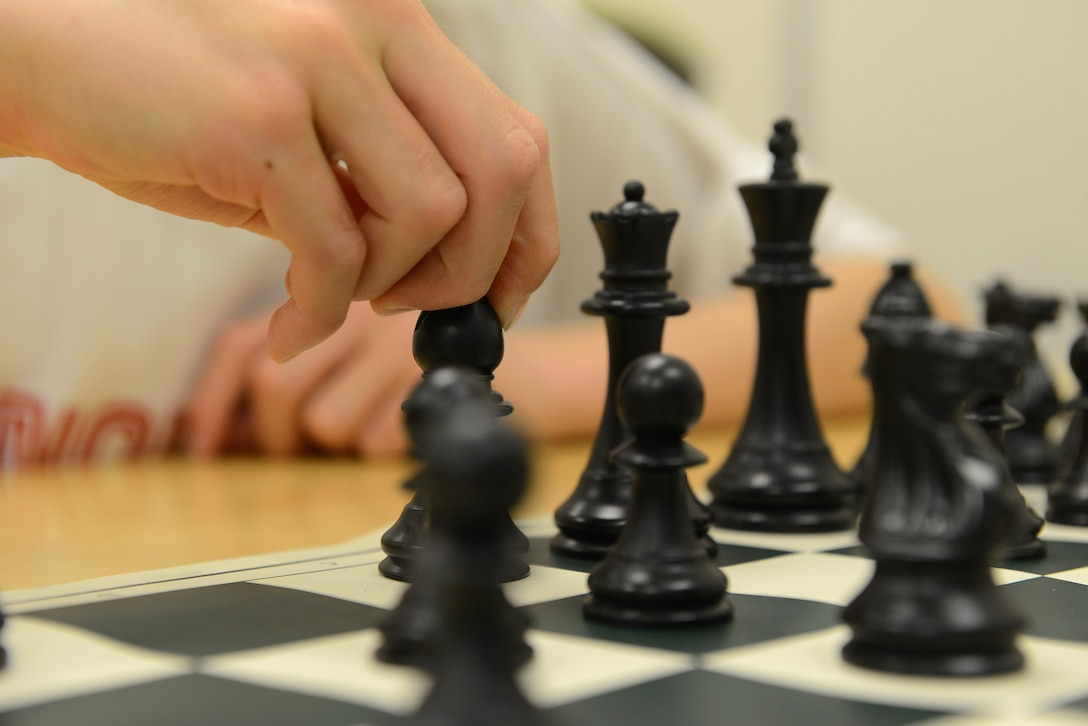 Caleb Hammon, 11-year-old son of U.S Air Force Lt. Col. Troy Hammon, U.S. Air Forces Central chief of contract and fiscal law, moves his bishop during a chess game at Shaw Air Force Base, S.C., July 22, 2014. Any child or adult wishing to learn how to play chess can participate in the chess club, which meets at the McElveen Resource Center every Tuesday. (U.S. Air Force photo by Airman 1st Class Diana M. Cossaboom/Released)