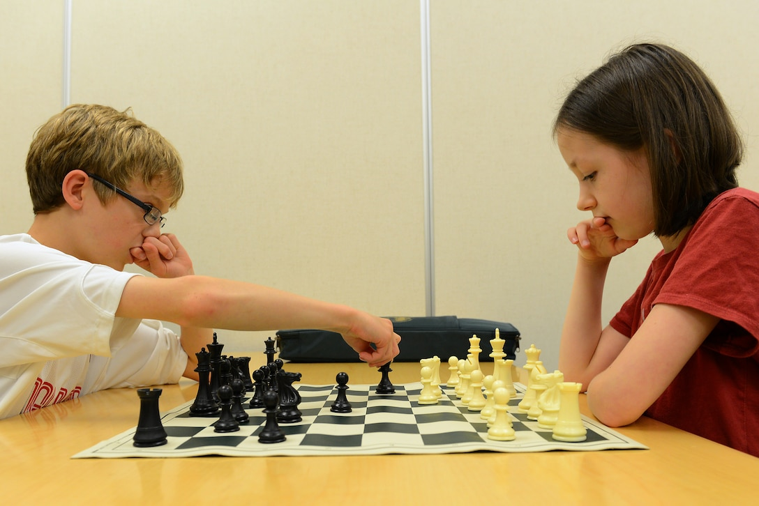 Caleb Hammon, 11-year-old son of U.S Air Force Lt. Col. Troy Hammon, U.S. Air Forces Central chief of contract and fiscal law, and Victoria Hobbs, 9-year-old daughter of Staff Sgt. Sharla Hobbs, 31st Intelligence Squadron, Detachment 1, senior tactics analyst, play chess at Shaw Air Force Base, S.C., July 22, 2014. The chess club is open to everyone, especially children ages 6 to 12. (U.S. Air Force photo by Airman 1st Class Diana M. Cossaboom/Released)