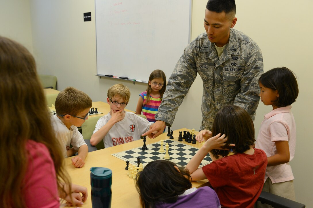U.S. Air Force 1st Lt. Martin Caluag, 77th Fighter Squadron chief of intelligence, teaches children strategies for chess in the chess club at Shaw Air Force Base, S.C., July 22, 2014. Caluag taught the children the differences between checkmate and stalemate before letting them play each other. (U.S. Air Force photo by Airman 1st Class Diana M. Cossaboom/Released)