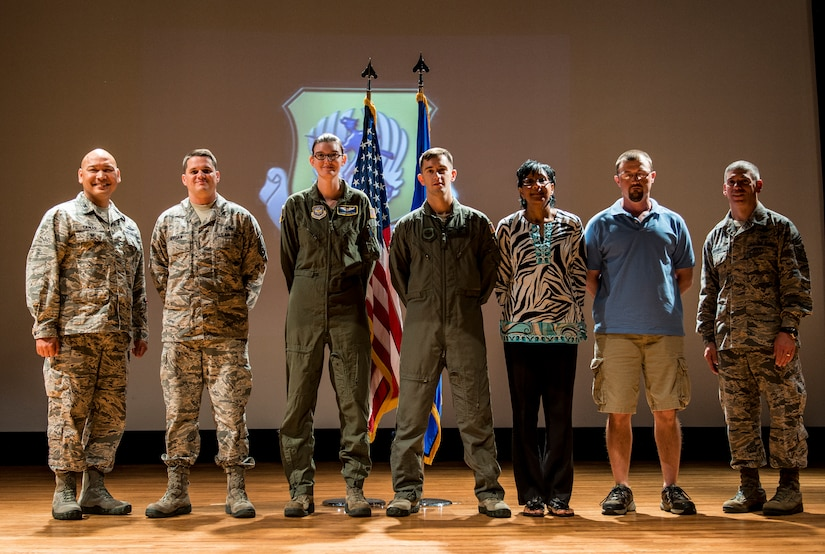 Colonel Jimmy Canlas, 437th Airlift Wing vice commander (left) and Chief Master Sgt. Shawn Hughes, 437th AW command chief (right), congratulate (left to right) Master Sgt. Adam Morgan, Senior Noncommissioned Officer in Charge of the Quarter, Airman 1st Class Stephanie Lucas, Airmen of the Quarter, Staff Sgt. Tyler Wehrung, Noncommissioned Officer in Charge of the Quarter, Faye Ellison, Civilian Category I of the Quarter and Vincent Moseley, Civilian Category II of the Quarter July 24, 2014, during the 437th AW Quarterly Awards ceremony at the Air Base Theater on Joint Base Charleston, S.C. Capt Daniel Naske, Company Grade Officer of the Quarter was unable to attend the ceremony. (U.S. Air Force photo/ Senior Airman Dennis Sloan)
