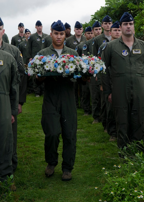 First Lt. Daniel Adams carries a wreath during the annual Raider 21 memorial ceremony July 21, 2014, in Adelup, Guam. Members of Team Andersen joined together with Government of Guam representatives to remember the six Airmen who lost their lives when a B-52 Stratofortress that had the Raider 21 call sign crashed off the coast of Guam July 21, 2008.  (U.S. Air Force photo by Senior Airman Katrina M. Brisbin/Released)