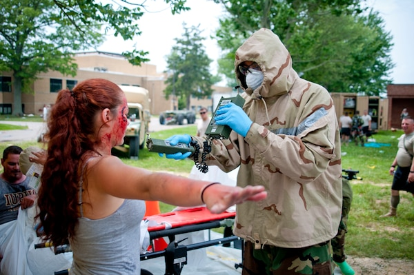 Army Spc. Tevin McAfee, from the 60th Engineer Company, 11th Engineer Battalion, Fort Benning, Ga., uses a radiation detector on Marley Bruce, a role player from Madison, Ind., after she exits a decontamination tent, July 23, 2014, as part of Vibrant Response '14 at Camp Atterbury, Ind. U.S. Army photo by Staff Sgt. Timothy Koster