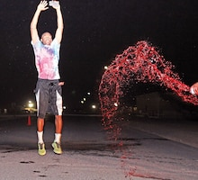 Spc. LaBarron Simmons, fire support specialist, HHC, 1st ABCT, jumps in the air as he is doused with red-colored water after finishing second in a 5K color run July 4 at Camp Buehring, Kuwait. Buehring's MWR sponsored the all-day event to help Soldiers relax for the Independence Day celebration.