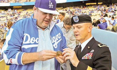 "Maj. Gen. Paul E. Funk II, 1st Inf. Div. and Fort Riley commanding general, shows actor Eric Stonestreet details on a ""Big Red One"" coin June 30 before the Los Angeles Dodgers versus Cleveland Indians game at Dodgers Stadium in Los Angeles."