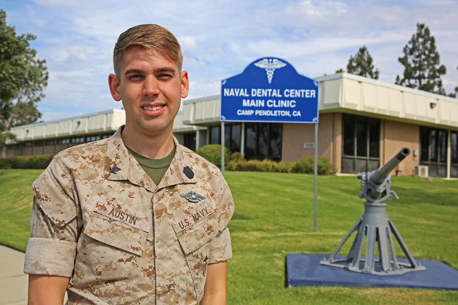 """Petty Officer 3rd Class Andrew Austin, a dental technician with 1st Dental Battalion, 1st Marine Logistics Group, stands in front the 13 Area Dental Clinic aboard Camp Pendleton, Calif., July 23, 2014. Dental technicians provide much needed assistance to dentists by setting up and maintaining  equipment, putting the patients at ease, preparing them for treatment and performing X-ray scans and administrative tasks. """"As dental technicians, we need to take care of patients' needs,"""" said Austin. """"We work hand-in-hand with the dentists for eight hours a day to provide those needs and maintain combat readiness."""""""