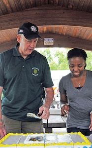 Garrison Chaplain (Col.) Harry Rauch, left, cuts the cake with Pvt. Whitney Ruffin, chaplains assistant, HHC, USAG Fort Riley, right, during Fort Riley's Chaplain Corps 239th Anniversary Celebration July 17 at Moon Lake. Rauch is the oldest current member of the Chaplain Corps at Fort Riley while Ruffin is the youngest.