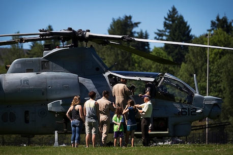 """Maj. Daniel """"Hungry"""" Hipol and Capt. Tony """"Mimbo"""" LaVista, AH-1Z Super Cobra attack helicopter pilots with Marine Light Attack Training Squadron 303, answer questions from Seattle-area residents after landing their Super Cobra helicopter at the University of Washington during a Marine Week Seattle community relations event in Seattle, July 28, 2014. Marine Week, held in Seattle for the first time from July 26 - August 3, is the Marine Corps' largest annual celebration of country, community and Corps. Hipol, 39, is from West Palm Beach, Fla., and LaVista, 32, is from Los Gatos, Calif. (U.S. Marine Corps photo by Sgt. Reece Lodder)"""