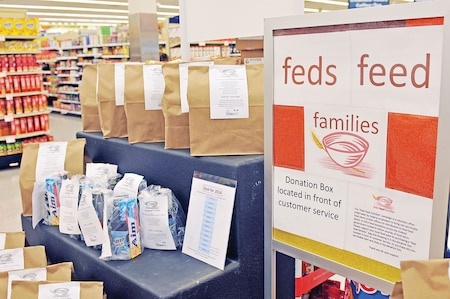 Brown paper bags sit filled with groceries and hygiene items, ready to by purchased and donated during the Feds Feed Families campaign which runs until the end of August at the Fort Riley commissary. The bags cost around $10 and can be easily purchased at the register and then dropped at the donation collection point before exiting the store.