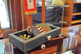 Fort Riley and patriotic themed coasters sit on display with thimbles ready for purchase at the museum's gift shop, located at the Cavalry Museum.