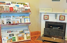 A shelf full of historical books sits on display by the fireplace ready for purchase at the museum's gift shop.