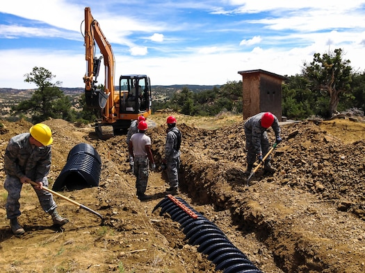 Six members of the 507th Civil Engineer Squadron perform earthwork with shovels and a backhoe at a home site on the Navajo Nation reservation in Gallup, N.M. in July.  The team partnered with a local charity and constructed homes for impoverished Indians as part of Innovative Readiness Training. (U.S. Air Force photo/1st Lt. Christopher Yates)