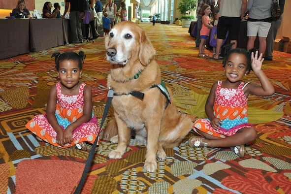 Tess, a Hope Animal-Assisted Crisis Response K-9, interacts with Geneviene and Elizabeth Cherington, daughters of Senior Master Sgt. Anthony Cherington, 482nd Maintenance Squadron flight chief, Homestead Air Reserve Base, Florida, during a Yellow Ribbon event in Orlando, Florida July 25, 2014. The Yellow Ribbon Program promotes the well-being of reservists and their families by connecting them with resources before and after deployments. (U.S. Air Force photo/Master Sgt. James Branch)