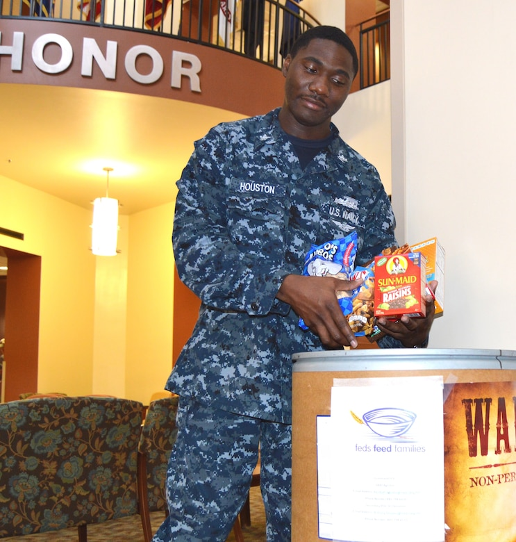 """Naval Health Clinic Charleston Petty Officer 2nd Class Anthony Houston, places non-perishable food items recently donated by NHCC staff members in a food collection barrel in the NHCC atrium at Joint Base Charleston, S.C. NHCC is participating in the """"Feds Feed Families"""" campaign to collect food and help combat hunger in our local communities. NHCC has one of several food collection barrels placed at commands around the Weapons Station. Last year the Weapons Station collected more than 3,240 pounds of food. This year's goal is to increase that amount by 10 percent. While food banks typically see large amounts of food on their shelves over the winter months, donations typically trail off after the holidays are over. Personnel wishing to donate have until the end of August to place non-perishable food items in the designated box in the atrium. Monetary donations may be made through the Religious Offerings Fund at the Weapons Station chapel. Each dollar is the equivalent to five pounds of food. (U.S. Navy Photo/Petty Officer 3rd Class Caralyn/Mulyk)"""