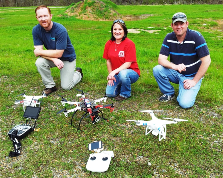 EL's team from the Environmental Risk Assessment Branch for unmanned aircraft systems  (EP-R-UAS) showing their remotely controlled  flying machines are, from left, Justin Wilkens with the Phantom 2 Vision; Jenny Laird with the Flamewheel F550; and Robbie Boyd with the second Phantom 2. Project managers can contact team members to schedule a demonstration of the UASs and learn about monitoring or sampling of dangerous or environmentally sensitive sites. EL photo.