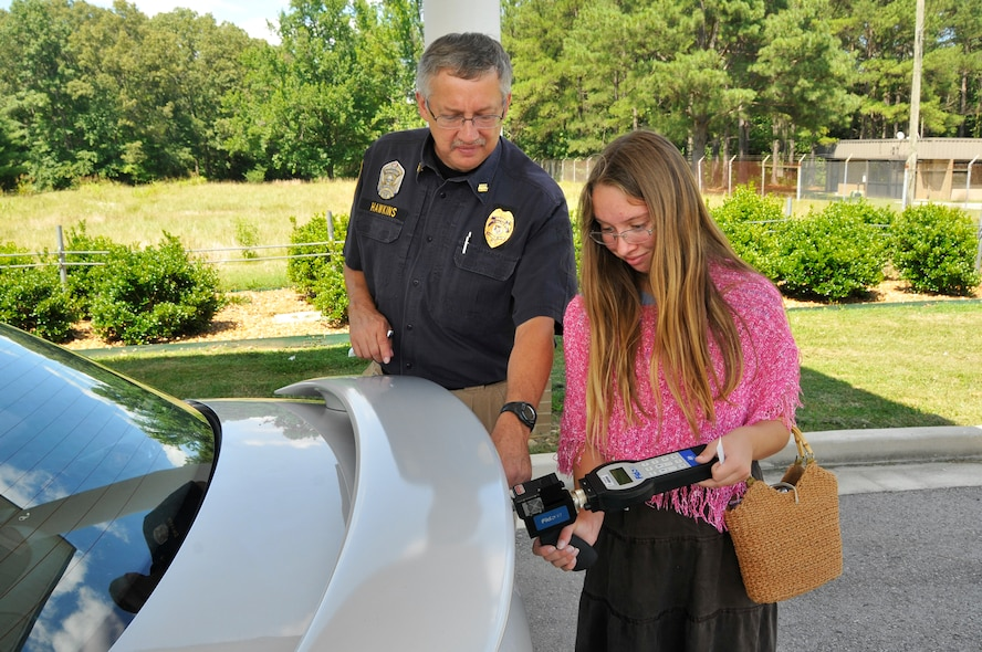 Katherine Hawkins, daughter of Dan Hawkins, operations officer for the Arnold Police Department, experiences firsthand the responsibilities of her dad's job. Here he shows Katherine how to use a Fido electronic explosive detector to check a vehicle for trace amounts of explosives.