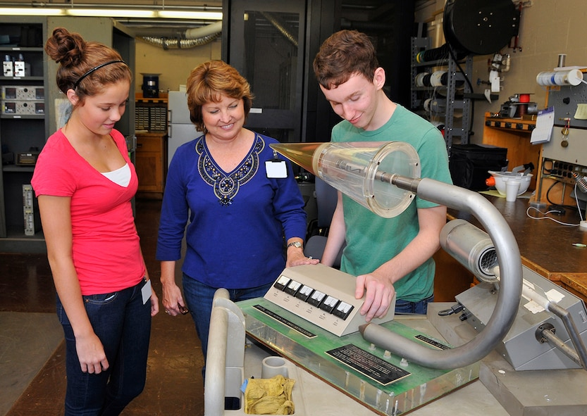 Alexis Loman and Samuel Oliver spent the day shadowing their mom, Susan Loman, group lead for the Data Processing and Analysis Development and Support Group, at the von Kármán Facility. Here Susan shows her son and daughter a balance simulator in the VKF lab.