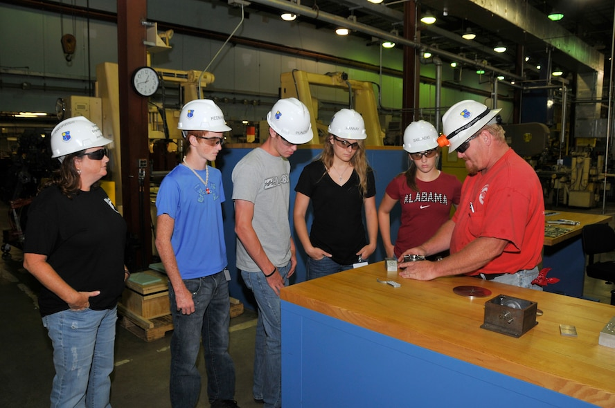 Arnold Engineering Development Complex (AEDC) personnel Joy and Dusty Rogers show a group of four Job Shadow Day participants around the Model and Machine Shop. Pictured are Zach Rogers, Peyton Punch, Hannah Newman and Sarah Petty watching as Dusty demonstrates how the parts to a two-piece water-cooled sting adapter work together.