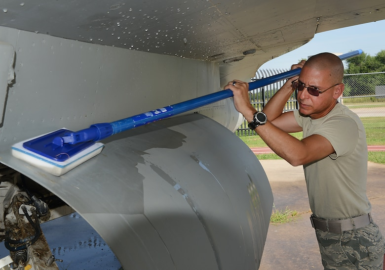 Chief Master Sergeant Dennis Dipiazzo, 138th Communications Flight Chief, scrubs the wheel doors of an F-16 static display aircraft at the Tulsa Air National Guard base, Tulsa Okla., 29 July 2014.  Members of the 138th FW Chiefs Council gathered to wash the static aircraft in an effort to keep them looking nice for public display.  (U.S. National Guard photo by Senior Master Sgt.  Preston L. Chasteen/Released)