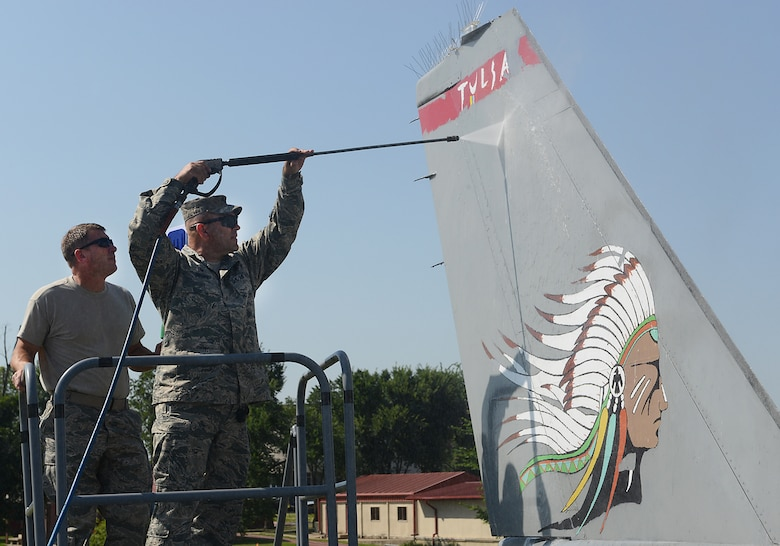 Lieutenant Colonel Travis Brown, 138th Maintenance Squadron Commander and Chief Master Sergeant Tracey Weaver, 138th Aircraft Maintenance Chief, power wash the tail of an F-16 static display aircraft at the Tulsa Air National Guard base, Tulsa Okla., 29 July 2014.  Members of the 138th FW Chiefs Council gathered to wash the static aircraft in an effort to keep them looking nice for public display.  (U.S. National Guard photo by Senior Master Sgt.  Preston L. Chasteen/Released)
