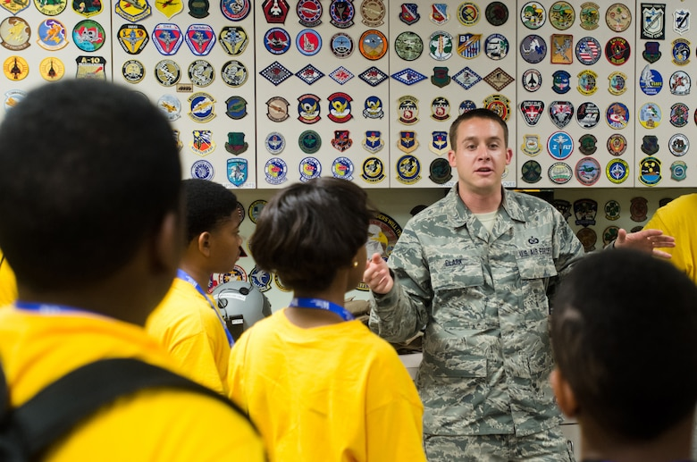 Tech. Sgt. David Clark, an aircrew flight equipment specialist for the Kentucky Air National Guard, answers questions from a group of local youths during a base-wide tour at the 123rd Airlift Wing in Louisville, Ky., on June 20, 2014. The visit was part of an aviation camp sponsored by the Organization of Black Aerospace Professionals designed to stimulate interest in the aerospace community. (U.S. Air National Guard photo by Senior Airman Joshua Horton)