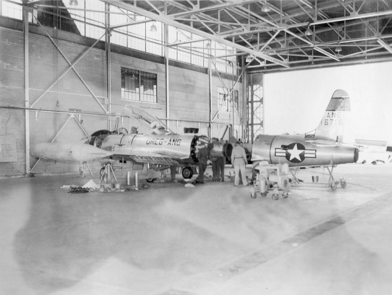 An OreANG Lockheed T-33A-1-LO Shooting Star jet trainer, serial number 51-6716, receives engine work in an aircraft maintenance hangar at Gowen Field during the OreANG's annual training, June 25, 1954.  (Courtesy 142FW History Archives)
