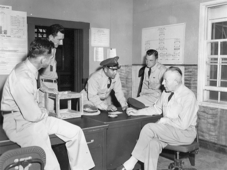 A meeting between members of the 142nd FIW and the Adjutant General of Oregon, Maj. Gen. Thomas E. Rilea, at Gowen Field, June 22, 1954.  From left to right, an unidentified officer sitting on desk, Lt. Col. Staryl Austin, Commander, 142nd FIG, Col. Frank Frost, Commander, 142nd FIW, Col. Gordon L. Doolittle, Deputy Chief of Staff, OreANG, with Maj. Gen. Rilea seated at right.  (Courtesy 142FW History Archives)