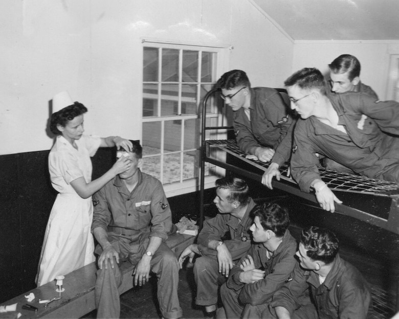 A Captain nurse of the 142nd Tactical Hospital demonstrates proper bandaging techniques to young Airmen at Gowen Field, June 1954. (Courtesy 142FW History Archives)