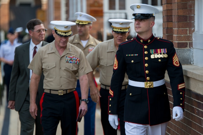 Staff Sgt. Matthew Phillips, ceremonial hoster, escorts guests to their seats during a retirement ceremony at Marine Barracks Washington, D.C., for Lt. Gen. Thomas Conant, deputy commander of U.S. Pacific Command, July 30.